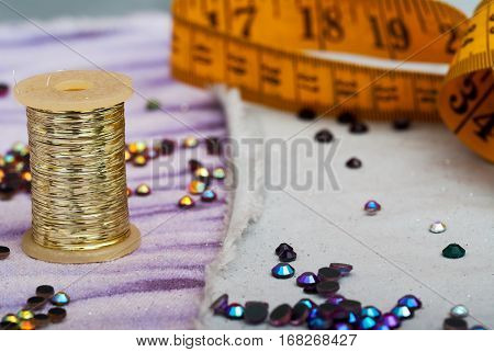 Sewing textile or cloth. Work table of a tailor. Measuring tape reel of thread and natural fabric. . Shallow depth of field. Focus reel of thread.