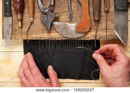 Leather craft tools on a wooden background. Craftmans working with leather using crafting DIY tools. Piece of hide and working handmade tools on a work table. Top view.