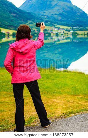 Tourist Taking Photo At Norwegian Fjord Lake