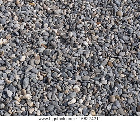 Gravel of gray and white round stones, abstract background texture / pattern.