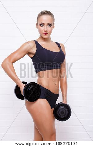 Side view of sexual muscular blonde posing with dumbbells on white textured brick background.