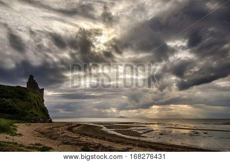 Greenan Castle on beach in cloudy sunset Scotland