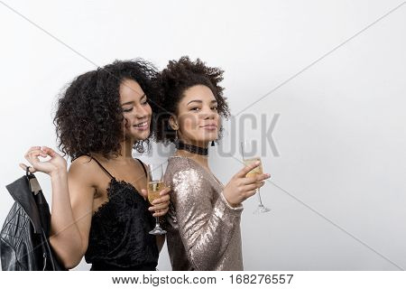 Two attractive female friends drinking champagne indoors