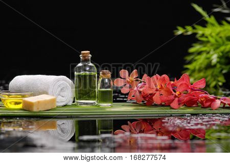 tranquil spa scene- orchid with candle ,oil green plant, towel,soap,