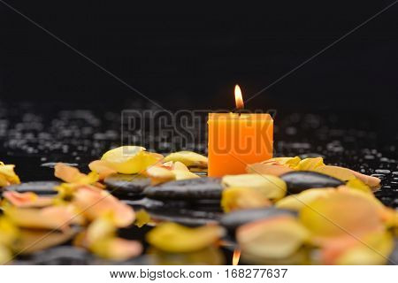 rose petals with orange candle and therapy stones
