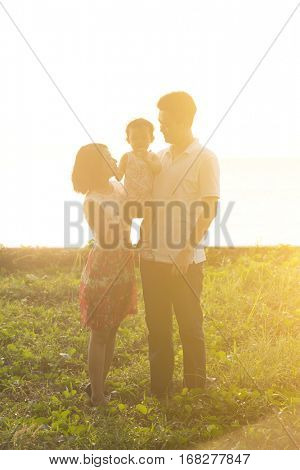 Happy Asian family enjoying outdoor activity together, standing on garden park in beautiful sunset during holiday vacations.