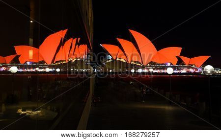 Sydney Australia - Jan 28 2017. Sydney Opera House and glass reflections at the end of the pier. Opera House bathed in red for Chinese Lunar New Year and welcoming the Year of the Rooster in 2017.