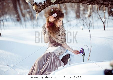 Fashion shoot of young beautiful girl in the winter forest