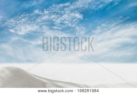 White snowdrift and snow-covered field on a background of blue sky with clouds on a winter day