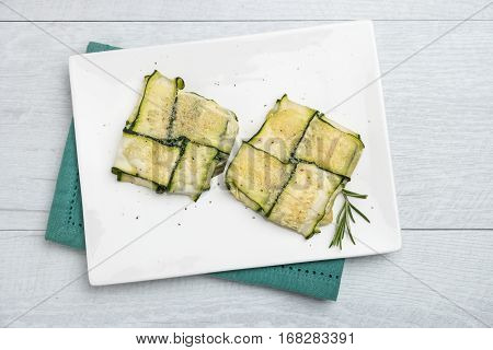 Oven baked courgettes stuffed with cheese garlic and herbs. Courgette recipe in the oven. Top view with copy space.