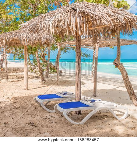 Two chairs await under a cabana at a quiet beach on the caribbean.