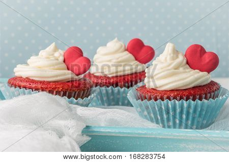 Red velvet heart cupcakes with cream cheese frosting and a red heart for Valentine's Day