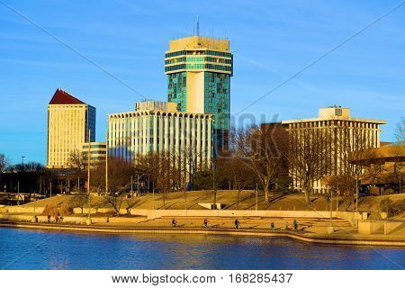 January 29, 2017 in Wichita, KS:  Highrise buildings which makes up the Wichita, KS Skyline beside the Arkansas River where people can enjoy walking on a pedestrian trail next to the river while observing the skyline