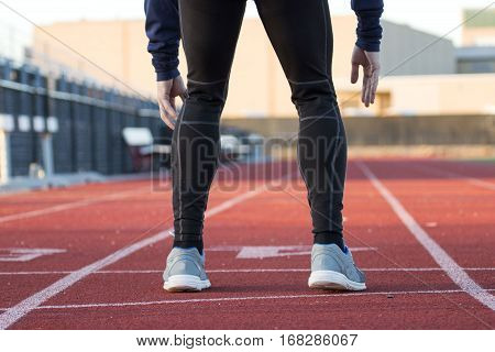 A runner in black spandex is ready to run on a red track