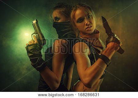 Two dangerous women fighters team with knife and gun. Tattoo on body.