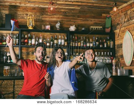 Cheerful friends emotionally watching soccer game in sport bar