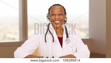 Senior African doctor smiling at camera sitting in office