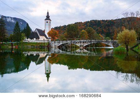 Church Tower And Stone Bridge At Lake Bohinj