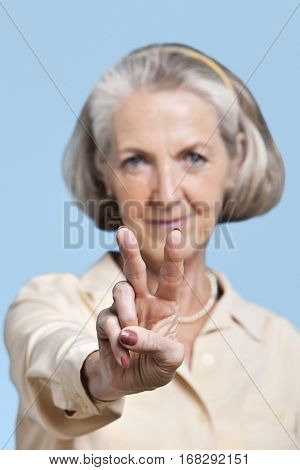 Portrait of senior woman in casuals gesturing peace sign against blue background