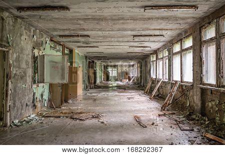 gloomy abandoned school corridor with debris and broken windows and doors in Pripyat