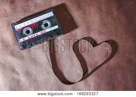 a cassette tape pulled out in the shape of a heart with a long shadow toned with a retro vintage instagram filter app or action effect on a brown paper textured background