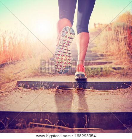 woman with athletic pair of legs going for a jog or run during sunrise or sunset up stairs in the mountains, healthy lifestyle concept  toned with a retro vintage instagram filter app or action effect