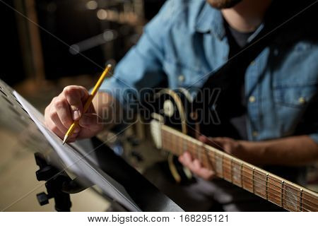 people, art and entertainment concept - man with guitar writing notes to music book at studio