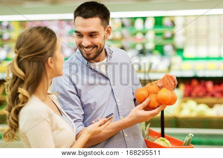 shopping, food, sale, consumerism and people concept - happy couple buying oranges at grocery store or supermarket