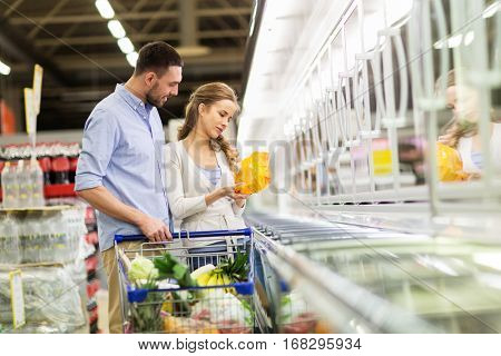 sale, consumerism and people concept - happy couple with shopping cart buying frozen food at grocery store or supermarket