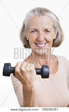 Portrait of smiling senior woman with dumbbell against white background