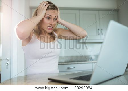 Pretty blonde woman looking at laptop at home