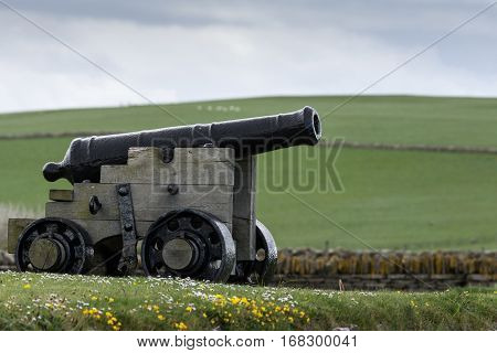 Orkneys Scotland - June 5 2012: A black historic cannon stands in the wider area around Skara Brae Neolithic settlement standing in green meadow with white and yellow wild flowers. . White-blue sky.
