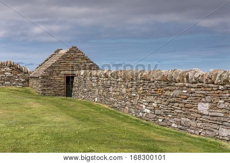 Orkneys Scotland - June 5 2012: Historic stone wall and restored house at Skara Brae Neolithic Settlement. Green lawn in front and all against blue sky with darker clouds.