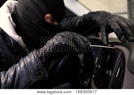 Thief in mask trying to steal car radio with screwdriver