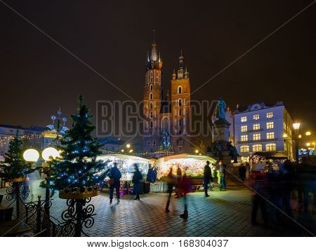 Krakow, Poland - December 19, 2016:: People visit Christmas market at main square in old city of Krakow, Poland