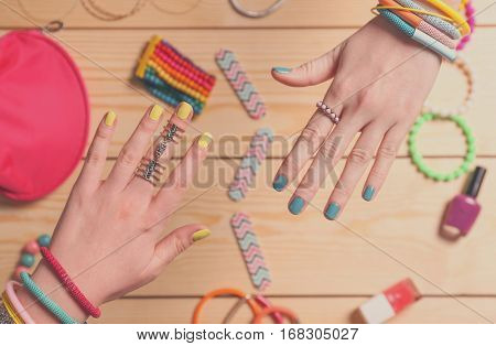 Female hands with beautiful nail art on wooden background