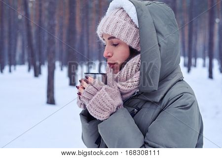 Close-up of concentrated woman blowing on hot tea to cool the liquid down. Blowing on a hot tea. Woman wearing warm scarf and mittens