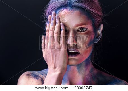 Portrait of beautiful young woman with amazing body-art on dark background