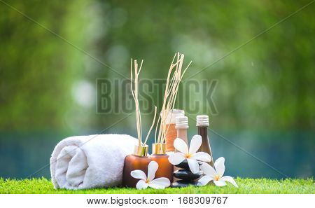 Spa treatment and product for hand and foot spa with flowers and water wooden background; select and soft focus; Spa herbal compressing ball white frangipani flowers Thailand. Greenery tone 2017