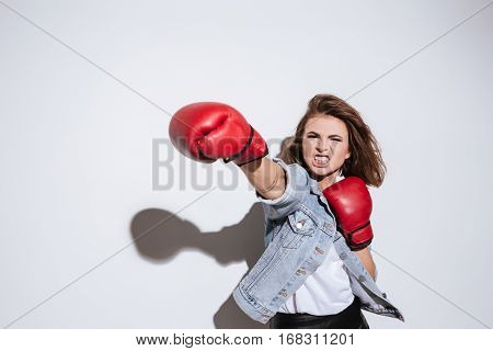 Photo of angry woman boxer dressed in jeans jacket and gloves make boxing exercise isolated over white background