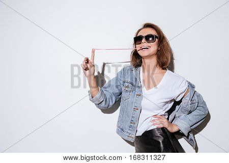 Picture of a young woman dressed in jeans jacket wearing sunglasses standing isolated over white background while stretching bubble gum.