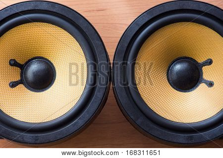 Bare audio speakers with amber colored fiber glass or aramid fiber cone ,on a work table. Shallow depth of field.