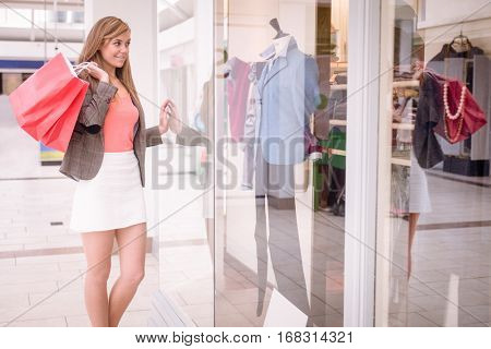 Beautiful woman window shopping in mall