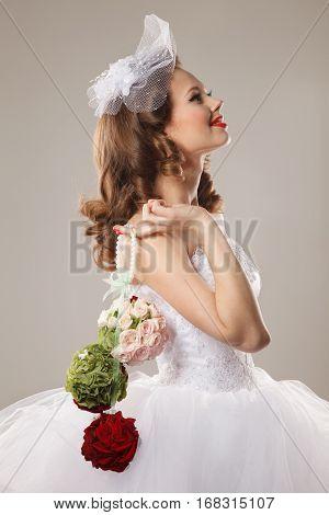 Pin-up bride holds a bouquet.Professional make-up hair and style