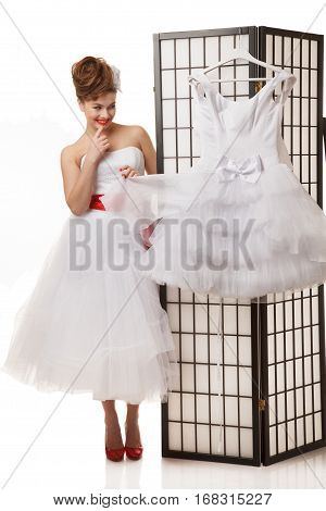 Pin-up bride standing near folding screen with another wedding dress hanging on it.Professional make-up hair and style.Isolated in white