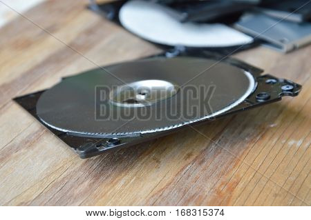 broken black diskette on the wooden board