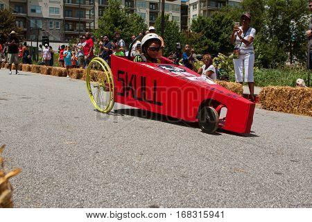 ATLANTA, GA - AUGUST 2016:  A kid steers his homemade car downhill in the Cool Dads Rock Soap Box Derby in the Old Fourth Ward in Atlanta GA on August 13 2016.