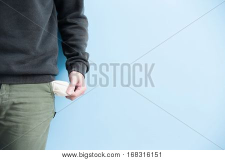 man showing his empty pockets demonstrating he has no money