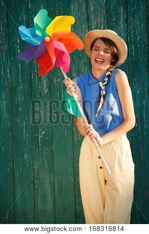 Young happy funny (vintage) dressed woman with colorful weather vane looking like flower Picture ideal for illustrating woman magazines.