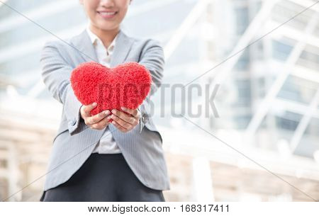 Close up of happy Asian female hands holding red heart and blurred on woman's smiling face with city and building background. Valentines Day love or working girl and good health concept. Copy space